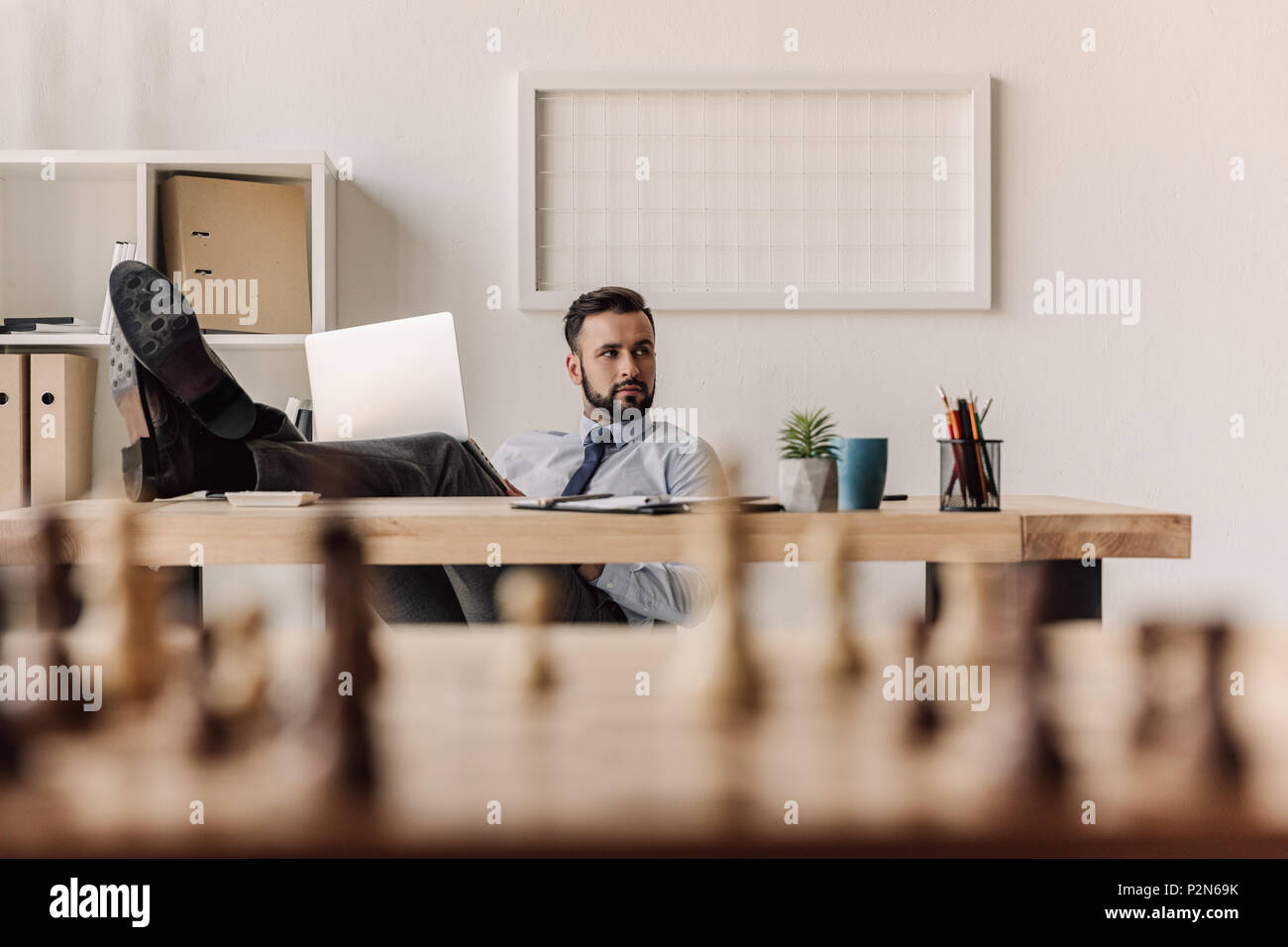 young bearded businessman working with laptop in modern office - Stock Image