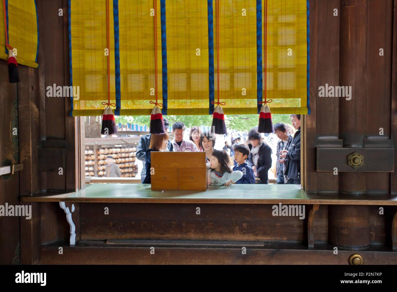 Japanese family drawing fortune telling paper at Meiji Shrine, Shibuya, Tokyo, Japan - Stock Image