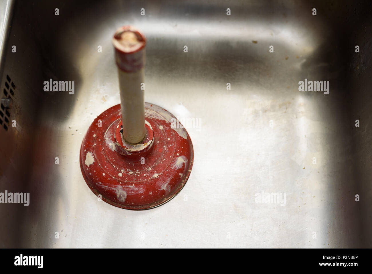 A plunger used to clean a clogged / blocked kitchen sink ...