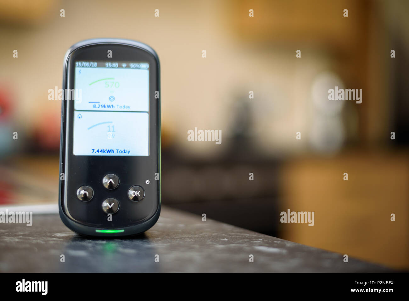 Domestic Energy Smart Meter on a Kitchen Worktop Displaying Energy Usage in Real Time - Stock Image