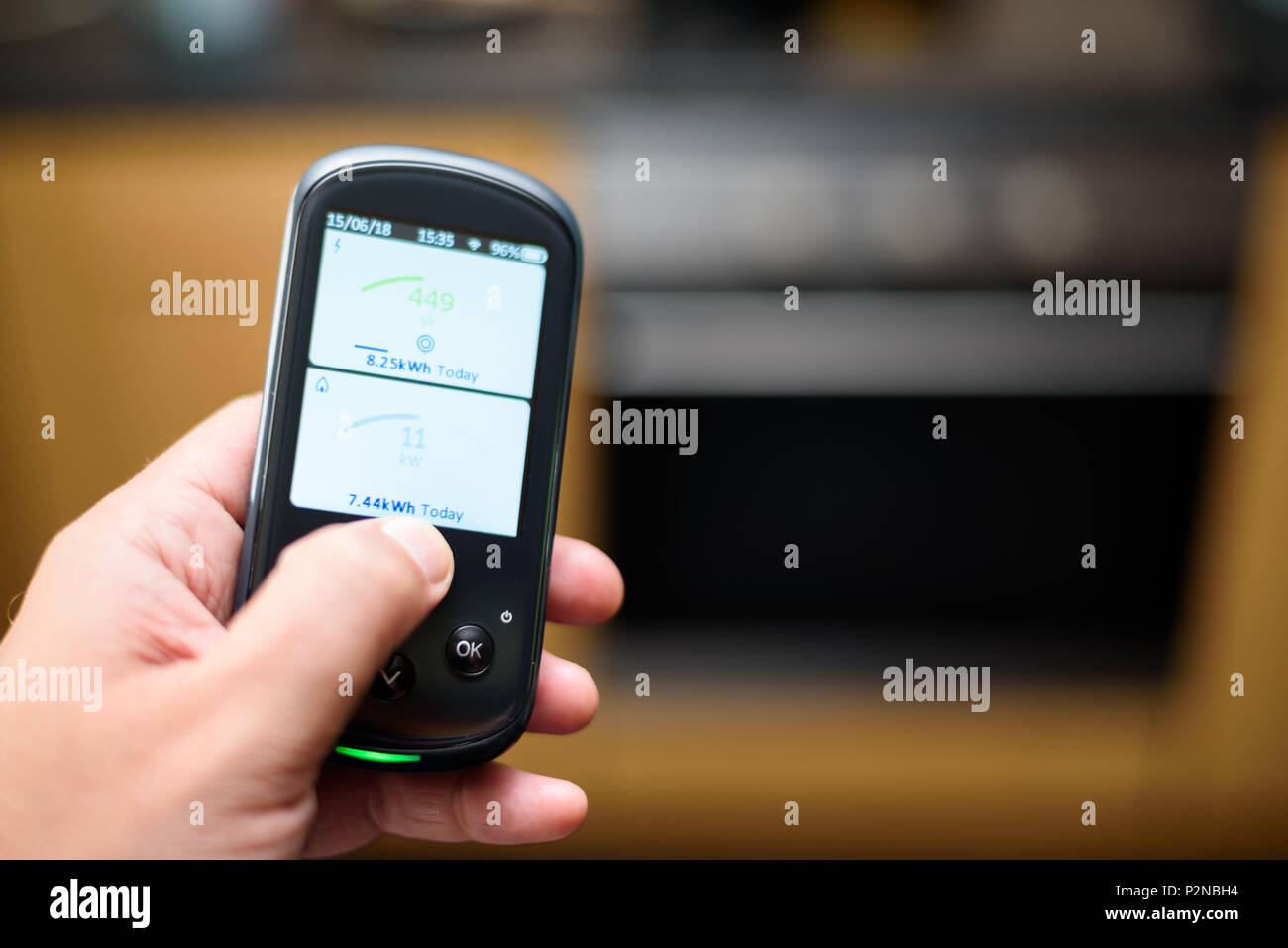Man holding a Domestic Energy Smart Meter unit in a kitchen, Displaying Energy Usage in Real Time - Stock Image