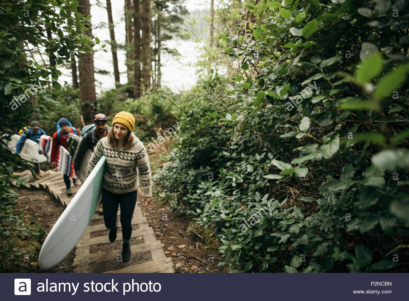 Friends enjoying weekend surfing getaway, carrying surfboards up stairs in woods - Stock Image
