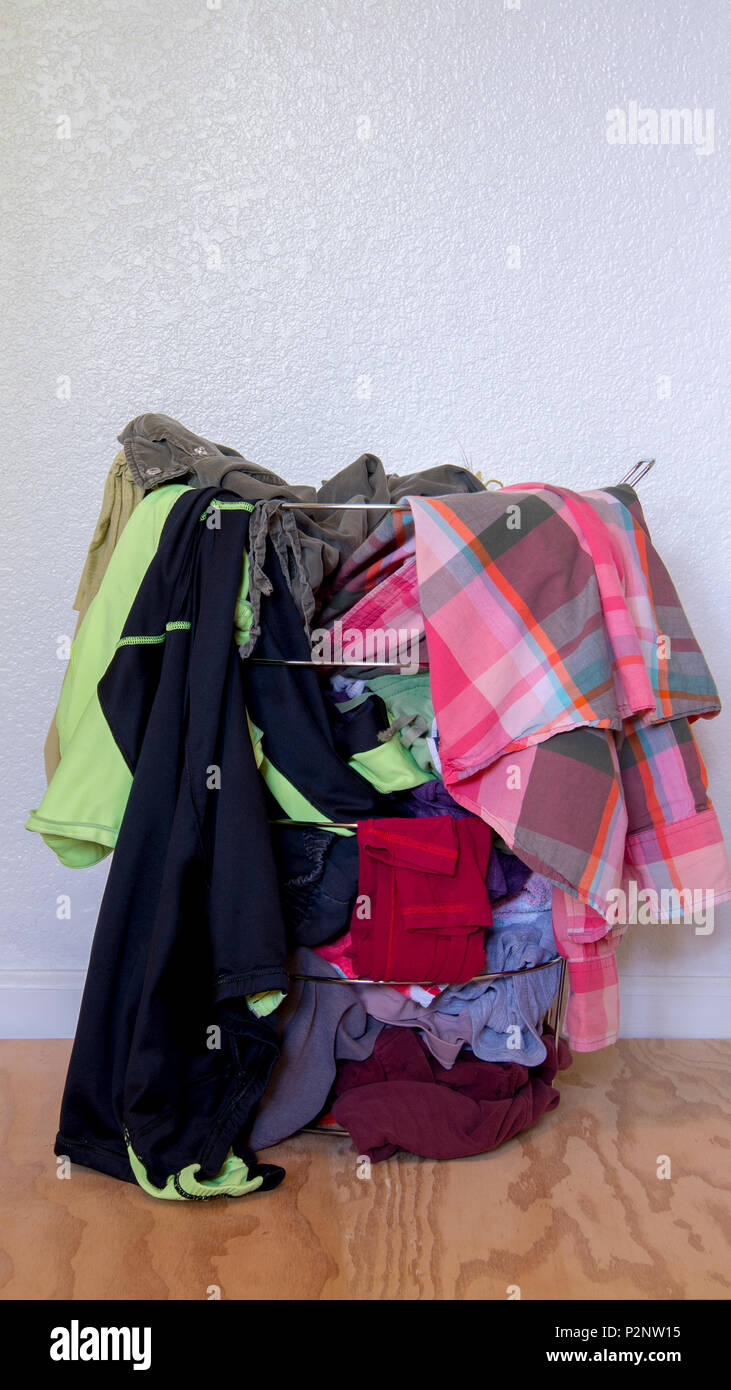 Metal laundry basket without a bag, full with colorful dirty clothes against white wall background, on wooden floor - Stock Image