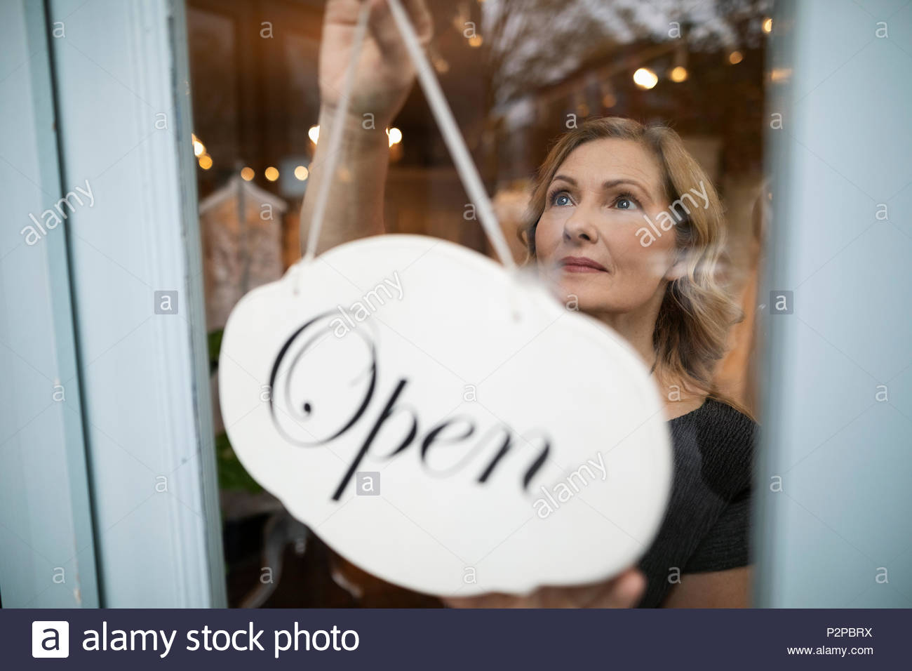 Bridal boutique owner hanging open sign in window - Stock Image