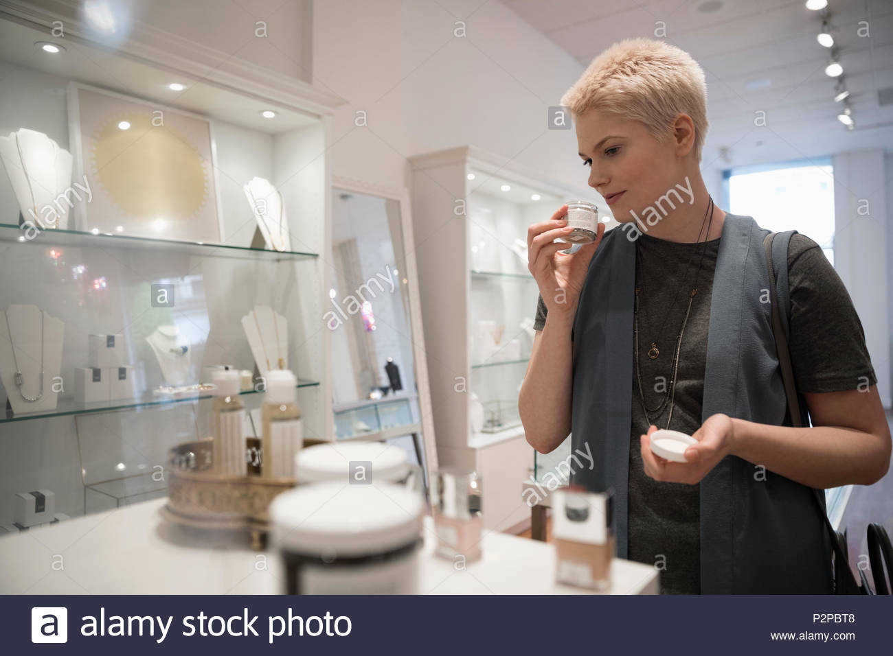 Young woman shopping for beauty products in boutique - Stock Image