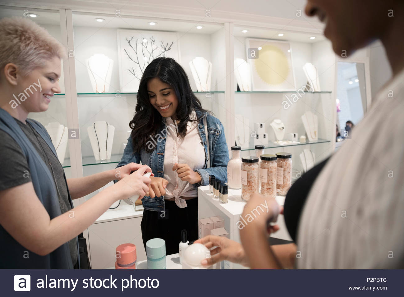 Young women friends trying on beauty products in boutique Stock Photo