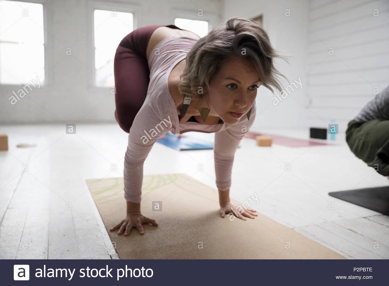 Focused woman practicing yoga crow pose in yoga class Stock Photo