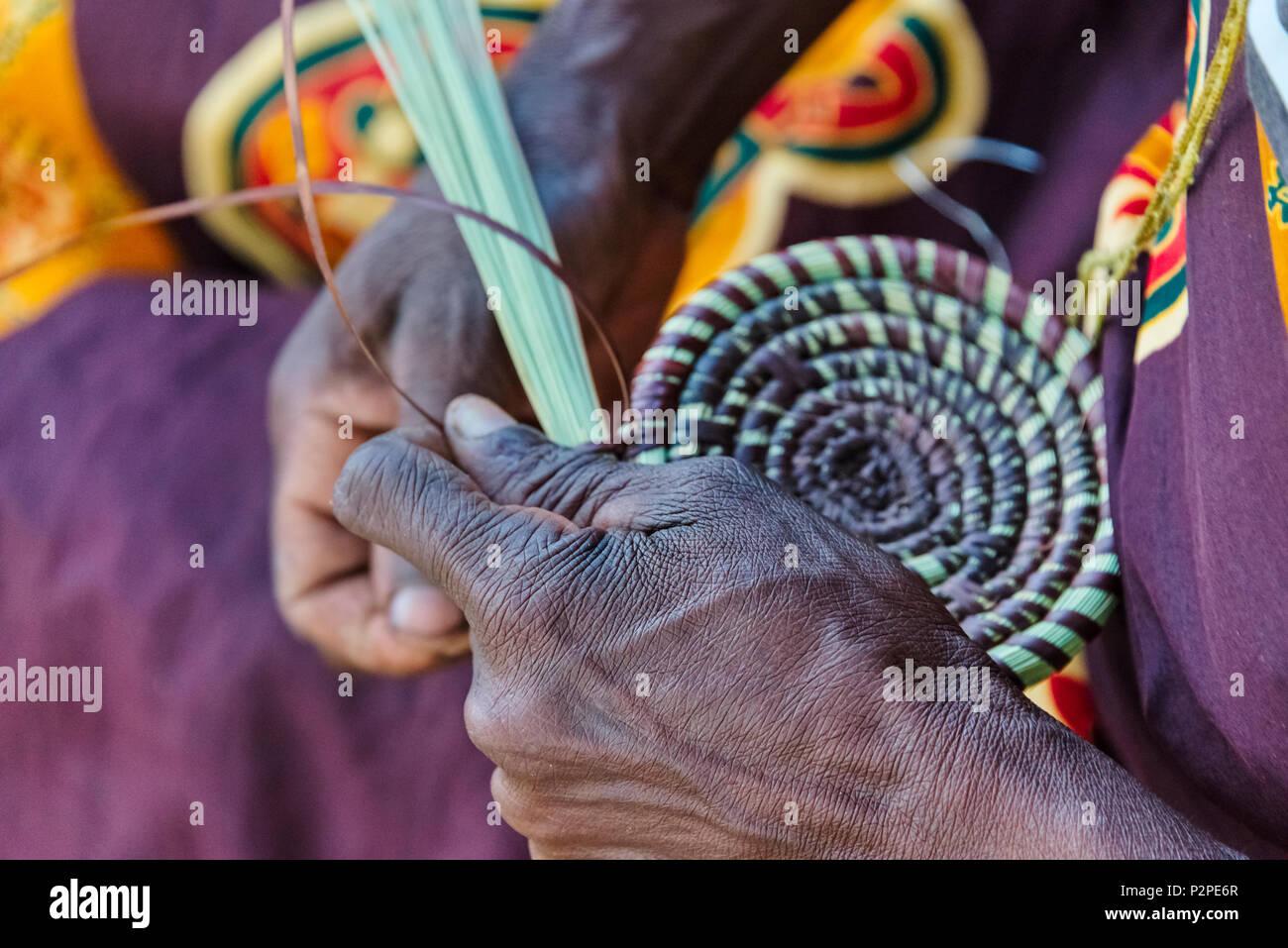 Mbukushu tribe woman weaving grass cushion, Kwando Traditional Village, Zambezi Region, Namibia - Stock Image