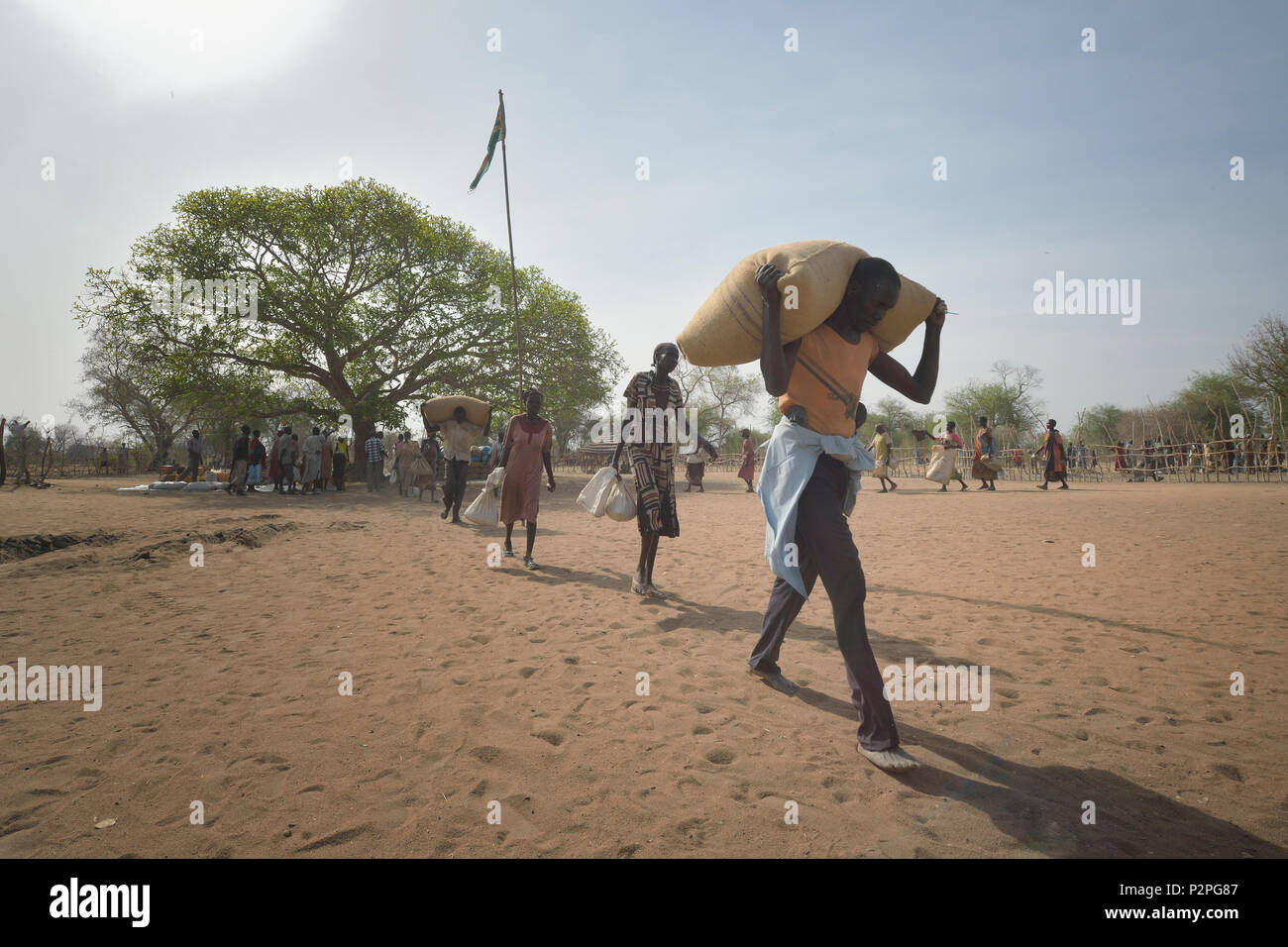 People receive food from the ACT Alliance on April 7, 2017, in Rumading, a village in South Sudan's war-plagued Lol State. - Stock Image