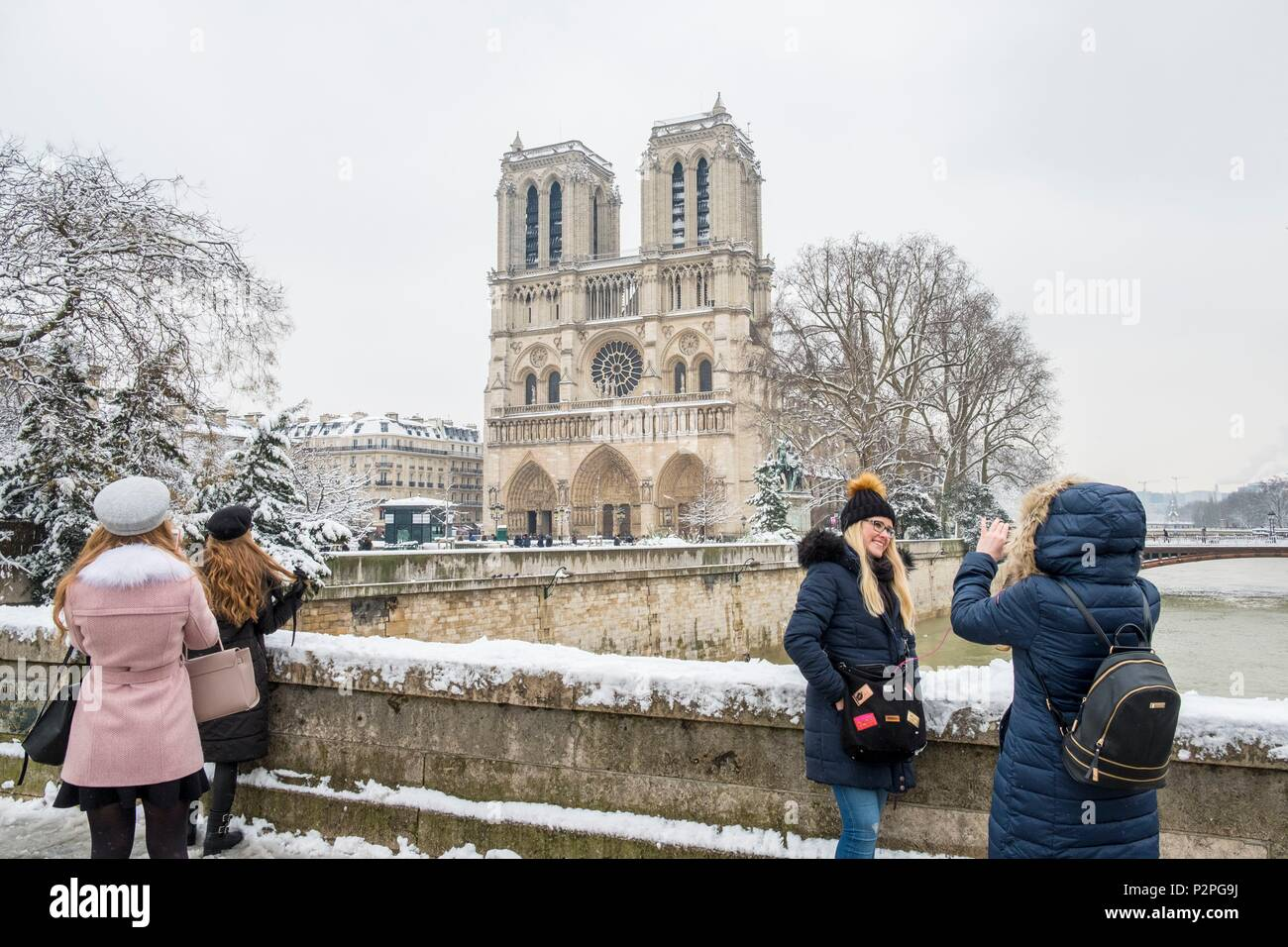 France, Paris, area listed as World Heritage by UNESCO, January 2018 flood, 2 tourists take a photo on the bridge at Le Double in front of Notre Dame cathedral, snowfalls on 07/02/2018 - Stock Image