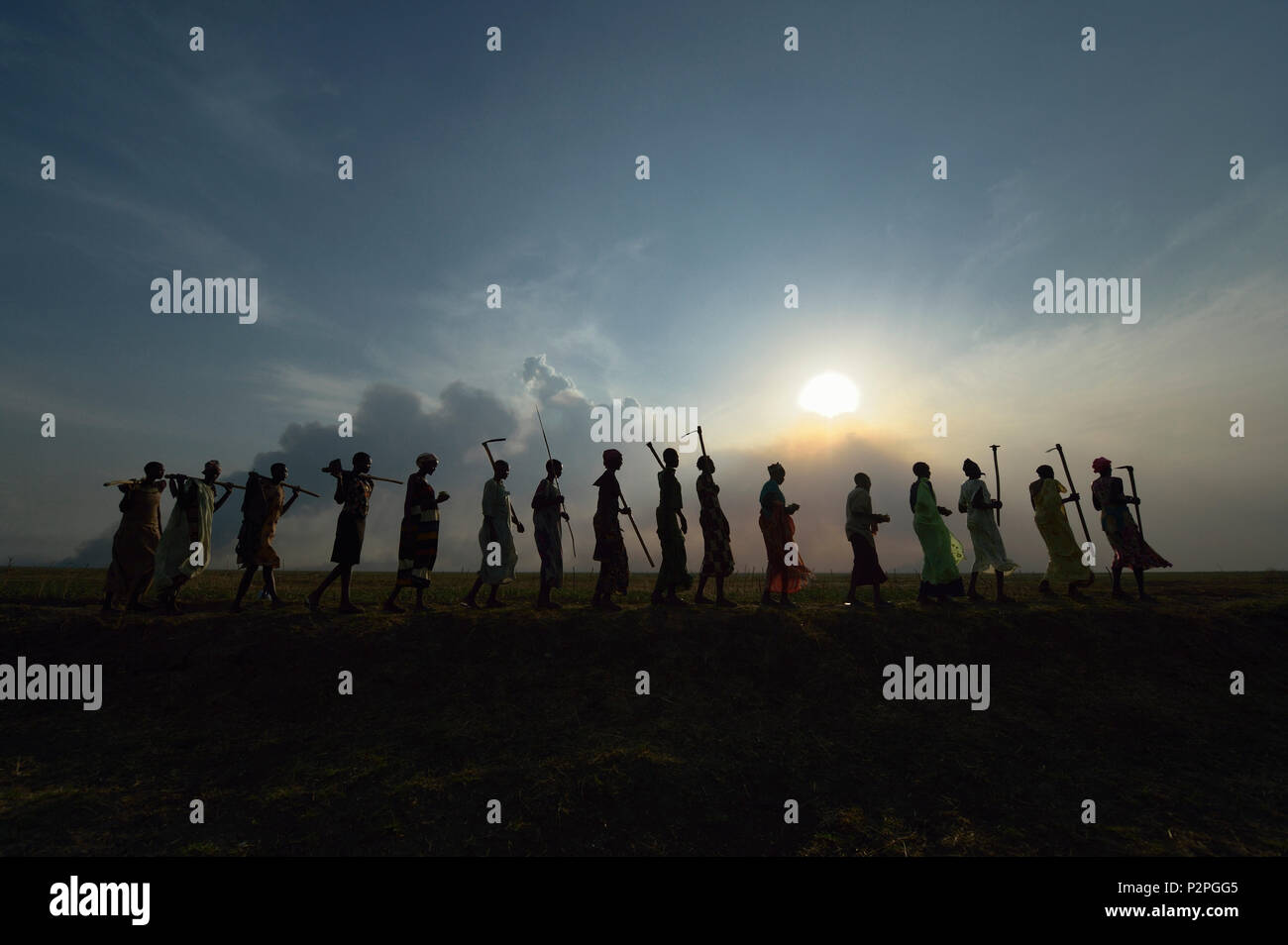 After working together in a community garden, women sing and dance as they walk home in Dong Boma, South Sudan, atop a dyke they constructed. - Stock Image