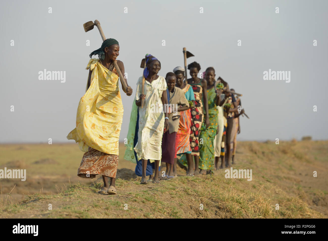 After working together in a community garden, Adhieu Deng Ngewei and her neighbors sing and dance as they walk home in Dong Boma, South Sudan. - Stock Image