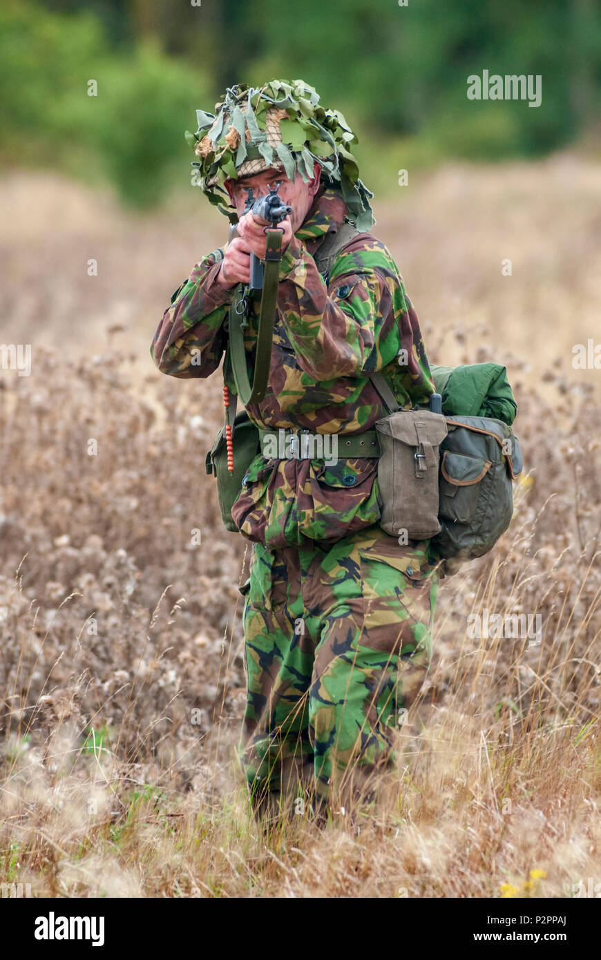 1970 – 1980 British Army soldier in camouflage suit and steel helmet carrying a SLR (Self-Loading Rifle) L1A1 - calibre of 7.62 mm (Posed by Actor) - Stock Image