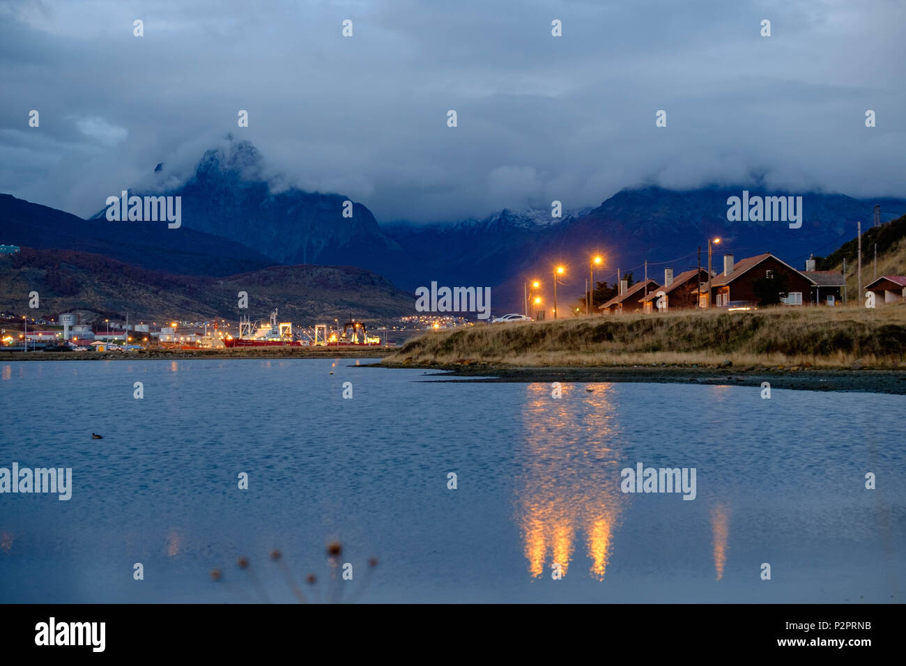 The 'Bahìa Encerrada' reflects some street lights in Ushuaia. In the background lies the small harbor, followed by the partly hidden mountains. Stock Photo