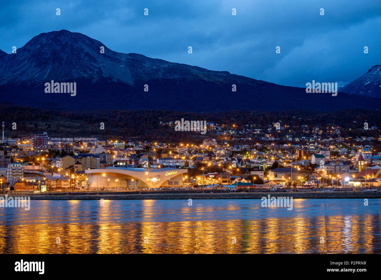 The 'Bahía Encerrada' reflects the city lights of Ushuaia. Close to the bay lies the casino. Higher up the hill, illegal housing creates a forest gap. Stock Photo