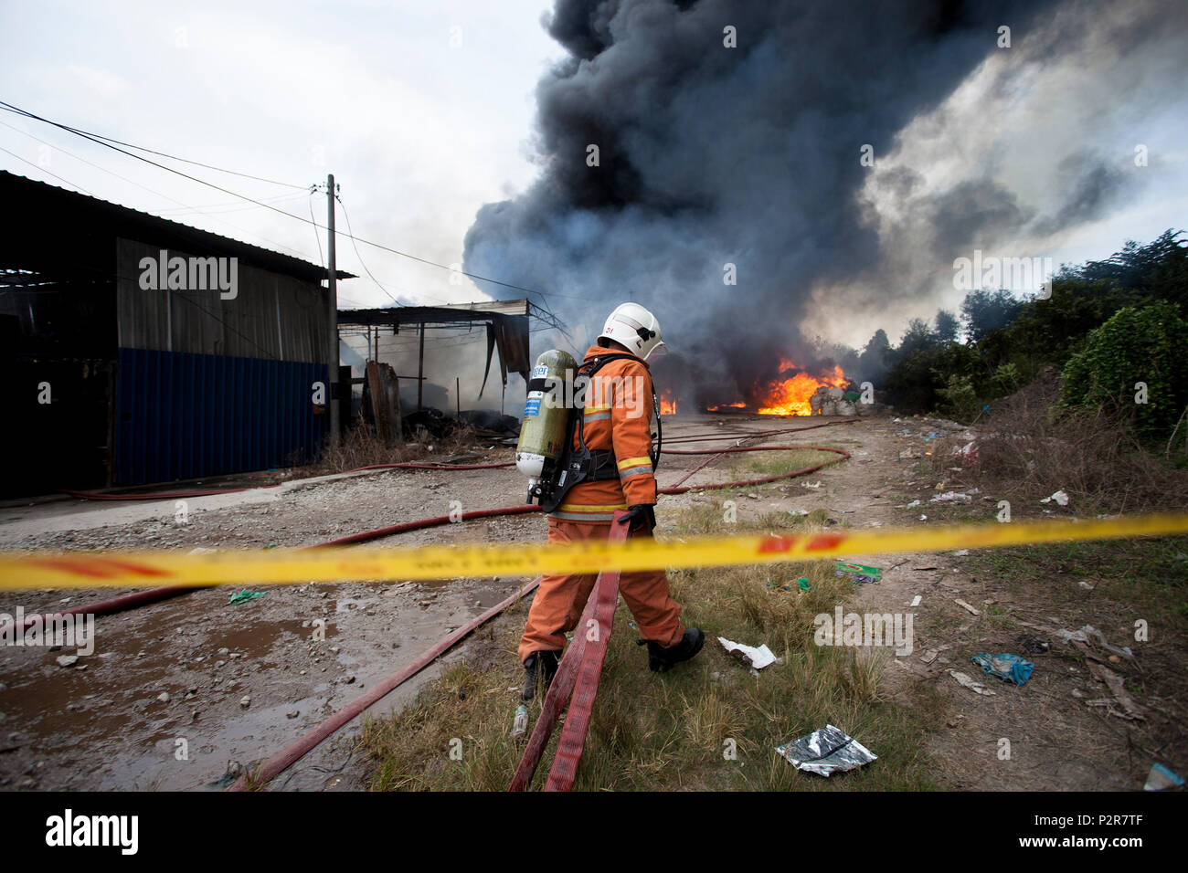 A fireman is pulling a firehose towards a burning factory in Sungai Petani. The fire broke at 1:00 PM and razed a plastic recycling centre, a plywood processing factory and a casket factory. More than 20 fire trucks were dispersed to control the massive fire due to wind condition and flammable products. - Stock Image