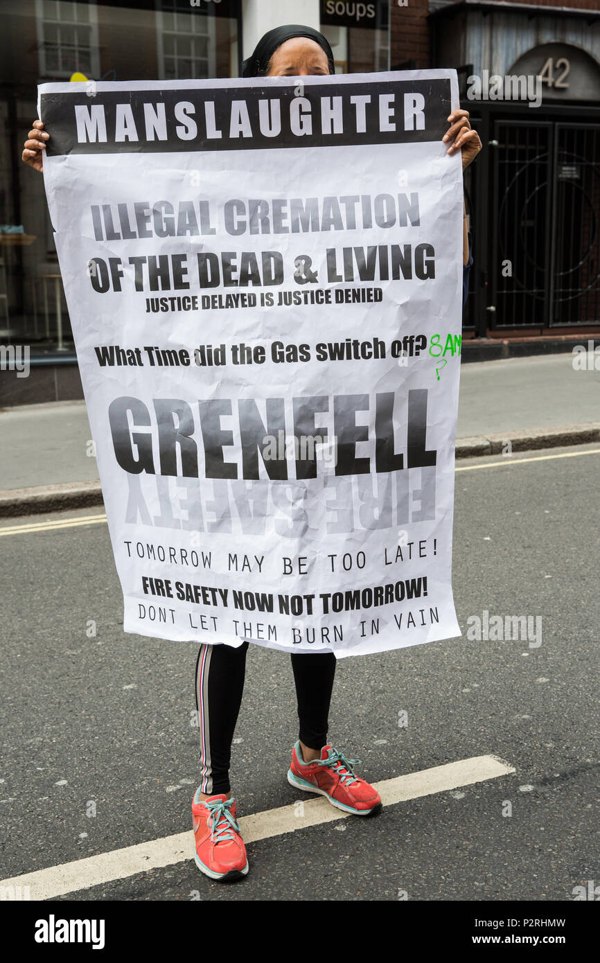London, UK. 16th June, 2018. A woman holds a poster in the street ...