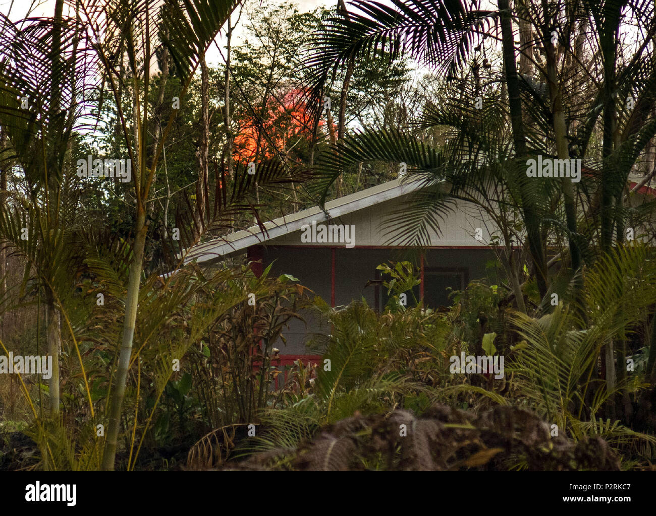 Pahoa, Hawaii, USA. 9th July, 2018. Fissure 8 erupts in the distance over a home in the Leilani Estates Subdivision as the Kilauea Volcano east rift zone eruption continues Sunday, June 10, 2018, in Pahoa, Hawaii. Photo by LE Baskow/LeftEyeImages Credit: L.E. Baskow/ZUMA Wire/Alamy Live News - Stock Image
