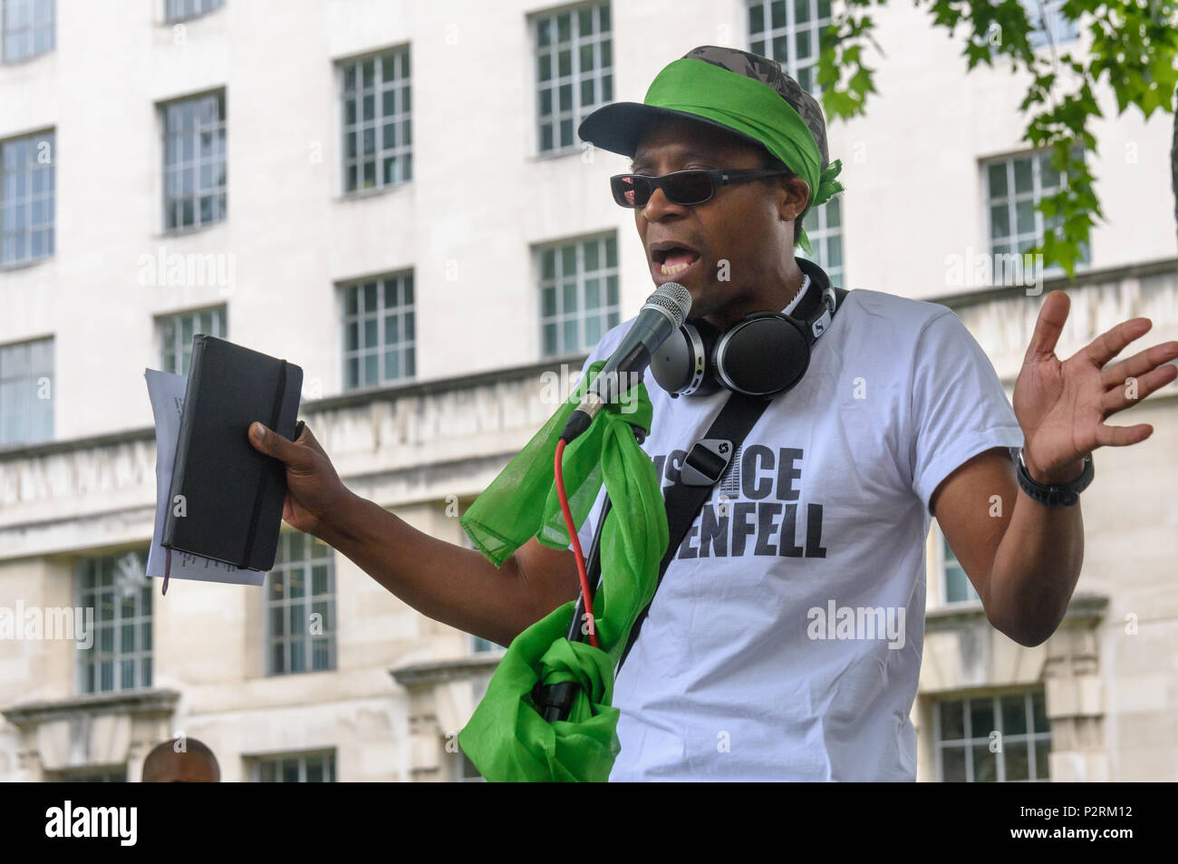London, UK. 16th June 2018. Barrister and Stand Up to Racism national officer Brian Richardson speaks to the  large crowd at Downing St showing solidarity with the 72 killed and the survivors of the Grenfell fire a year ago at a protest organised by Justice4Grenfell and the FBU (Fire Brigades Union.) After some speeches they marched to the Home Office for a brief protest before returning to Downing St for more speeches. Speakers complained of the many promises made by Theresa May which have been broken, despite her promise all survivors would be rehoused in 3 weeks, a year later 50% of survivo - Stock Image