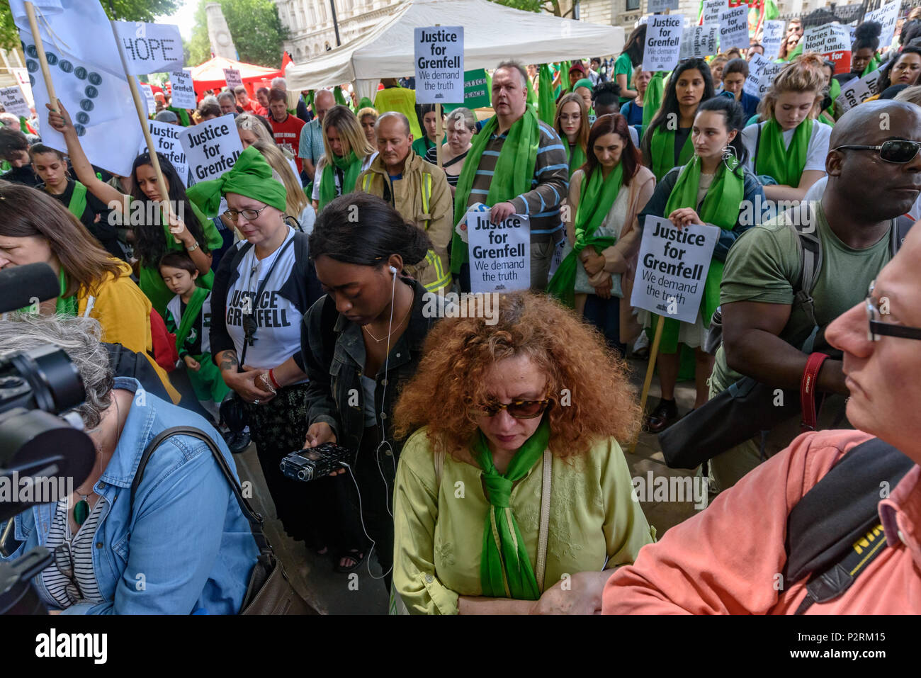 London, UK. 16th June 2018. People stand in a 72 second silence at Downing St remembering the 72 killed in the Grenfell fire a year ago at a protest organised by Justice4Grenfell and the FBU (Fire Brigades Union.) After some speeches they marched to the Home Office for a brief protest before returning to Downing St for more speeches. mmodation. 300 tower blocks across Credit: Peter Marshall/Alamy Live News - Stock Image