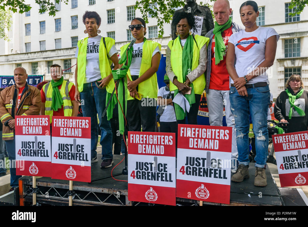 London, UK. 16th June 2018. Moyra Samuels, Tasha Brades and Yvette Williams from Justice4Grenfell and Matt Wrack and Lucy Masoud of the FBU stand in a 72 second silence at Downing St remembering the 72 killed in the Grenfell fire a year ago at a protest organised by Justice4Grenfell and the FBU (Fire Brigades Union.) After some speeches they marched to the Home Office for a brief protest before returning to Downing St for more speeches. Speakers complained of the many promises made by Theresa May which have been broken, despite her promise all survivors would be rehoused in 3 weeks, a year lat - Stock Image