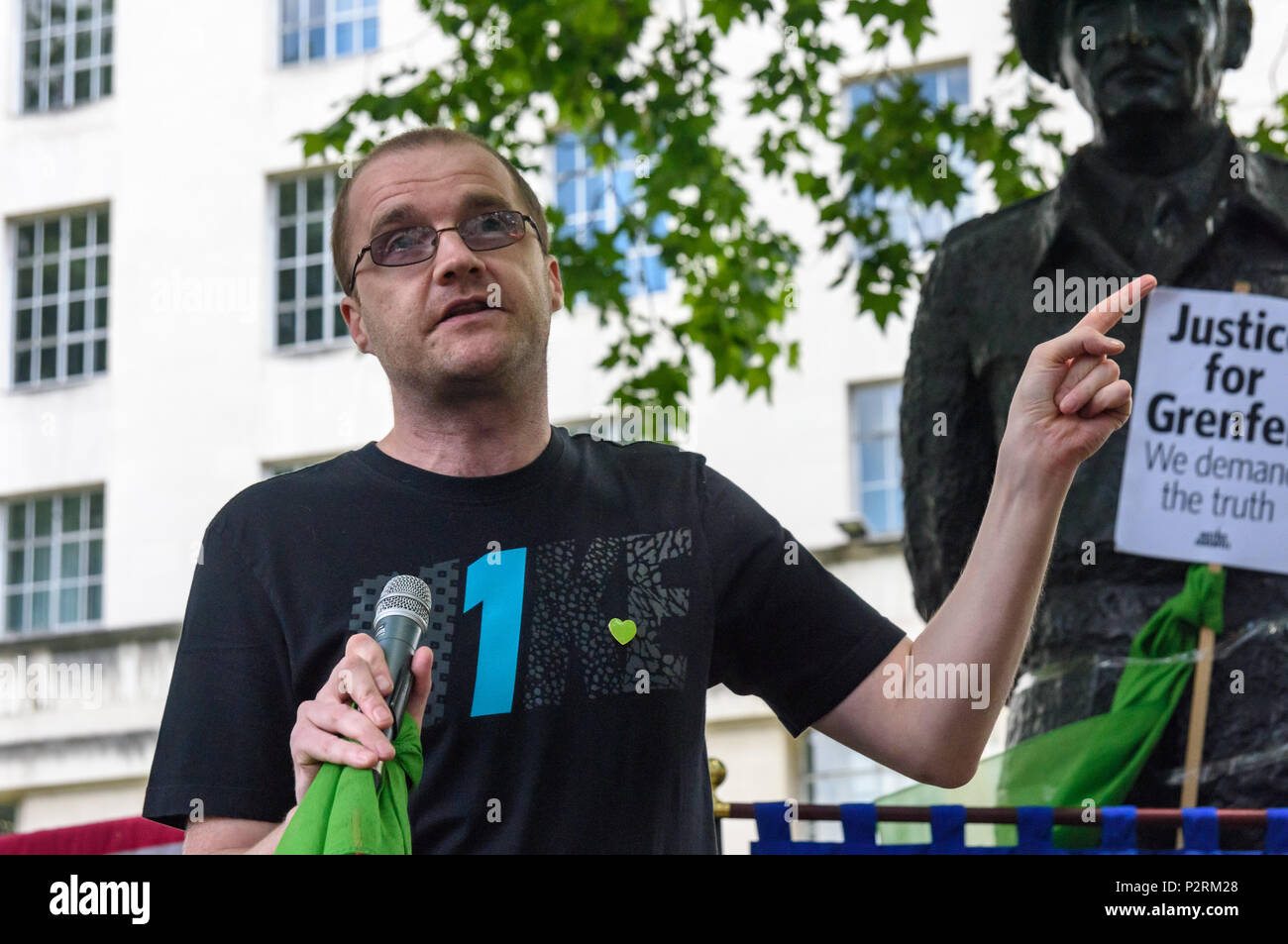 London, UK. 16th June 2018. Local resident Joe Delaney, displaced by the fire and still in temporary accommodation speaks at the protest at Downing St in solidarity with the 72 killed and the survivors of the Grenfell fire a year ago organised by Justice4Grenfell and the FBU (Fire Brigades Union.) After some speeches they marched to the Home Office for a brief protest before returning to Downing St for more speeches. Speakers complained of the many promises made by Theresa May which have been broken, despite her promise all survivors would be rehoused in 3 weeks, a year later 50% of survivors  - Stock Image