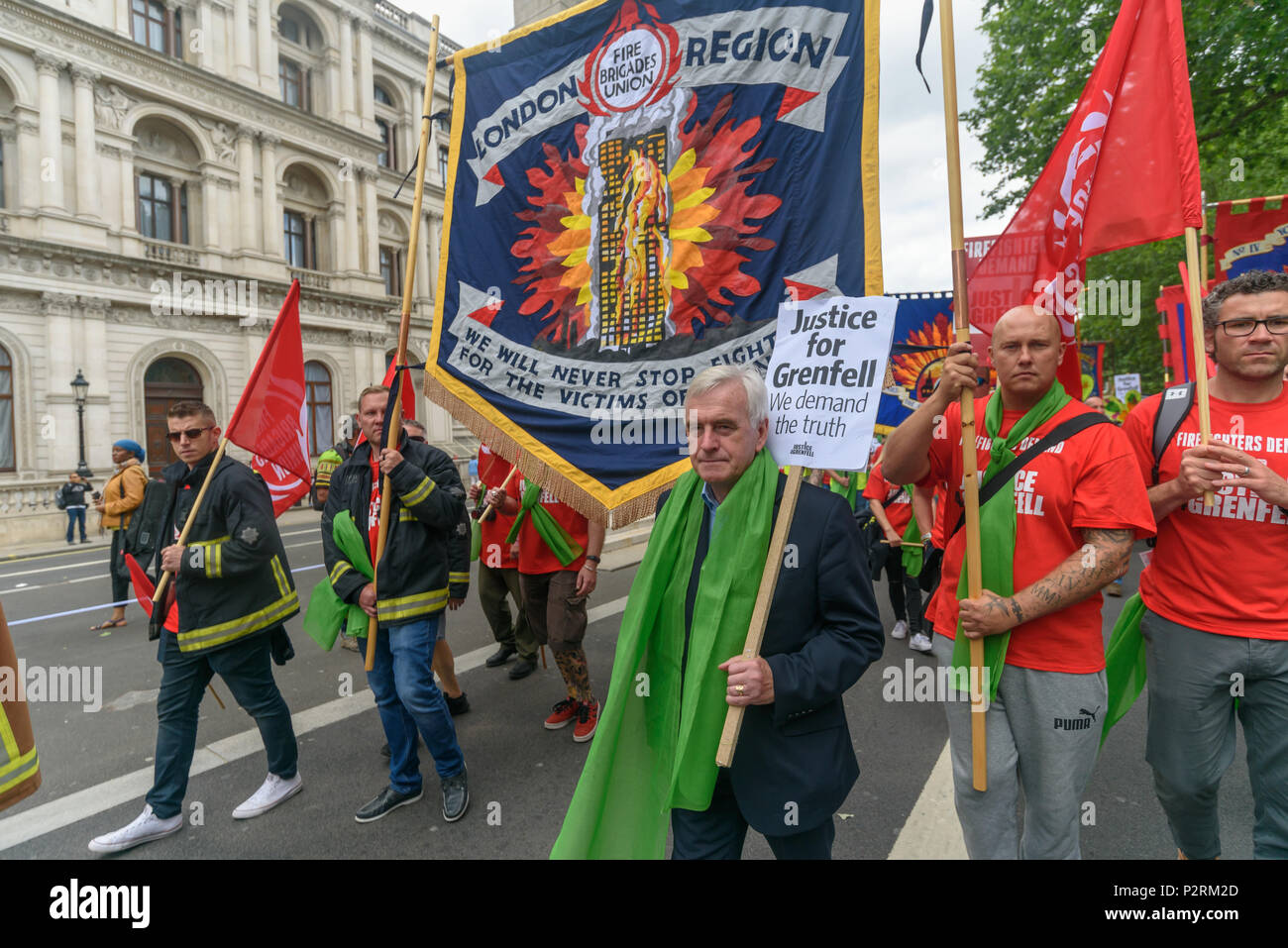 London, UK. 16th June 2018. Shadow Chancellor John McDonnell marches in the large crowd from Downing St to the Home Office in solidarity with the 72 killed and the survivors of the Grenfell fire a year ago at a protest organised by Justice4Grenfell and the FBU (Fire Brigades Union.) After some speeches they marched to the Home Office for a brief protest before returning to Downing St for more speeches. Speakers complained of the many promises made by Theresa May which have been broken, despite her promise all survivors would be rehoused in 3 weeks, a year later 50% of survivors and displaced f - Stock Image