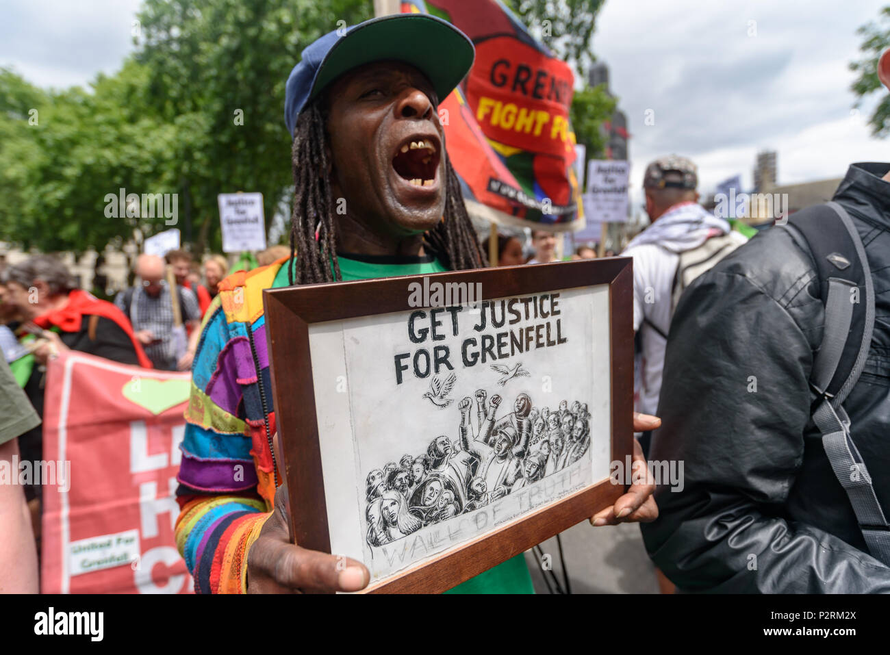 London, UK. 16th June 2018.  A man holds a framed picture with the message 'Get Justice For Grenfell' as he marches with the  large crowd from Downing St to the Home Office in solidarity with the 72 killed and the survivors of the Grenfell fire a year ago at a protest organised by Justice4Grenfell and the FBU (Fire Brigades Union.) After some speeches they marched to the Home Office for a brief protest before returning to Downing St for more speeches. Speakers complained of the many promises made by Theresa May which have been broken, despite her promise all survivors would be rehoused in 3 we - Stock Image