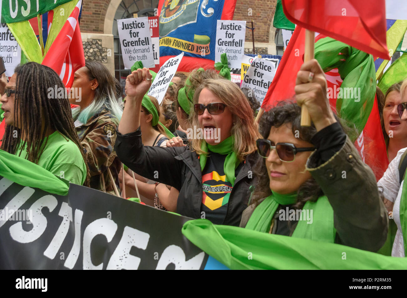 London, UK. 16th June 2018. People march back from the Home Office to Downing St in solidarity with the 72 killed and the survivors of the Grenfell fire a year ago at a protest organised by Justice4Grenfell and the FBU (Fire Brigades Union.) After some speeches they marched to the Home Office for a brief protest before returning to Downing St for more speeches. mmodati Credit: Peter Marshall/Alamy Live News - Stock Image