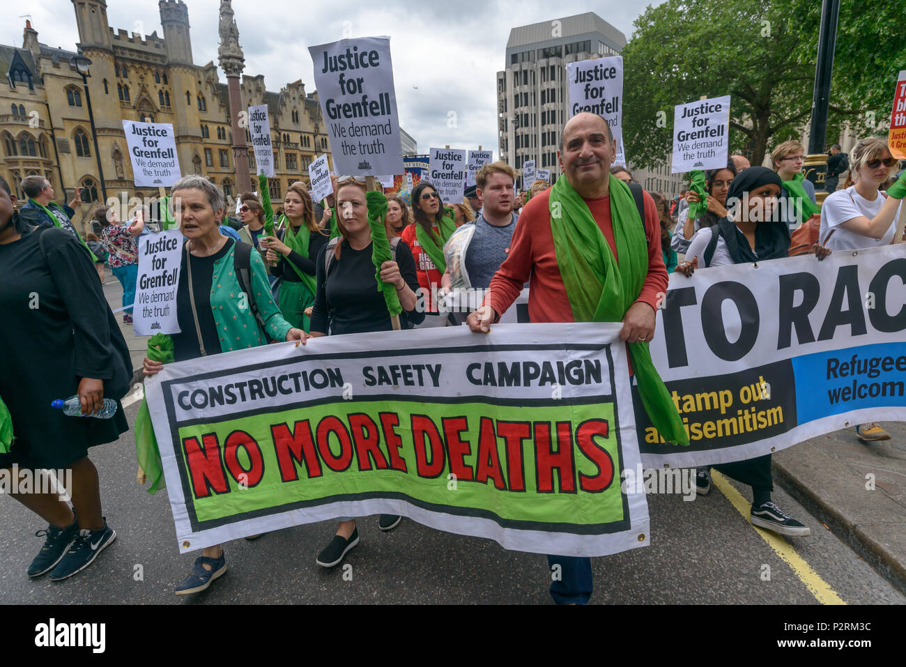 London, UK. 16th June 2018. People including the Construction Safety Campaign march back from the Home Office to Downing St in solidarity with the 72 killed and the survivors of the Grenfell fire a year ago at a protest organised by Justice4Grenfell and the FBU (Fire Brigades Union.) After some speeches they marched to the Home Office for a brief protest before returning to Downing St for more speeches. Speakers complained of the many promises made by Theresa May which have been broken, despite her promise all survivors would be rehoused in 3 weeks, a year later 50% of survivors and displaced  - Stock Image
