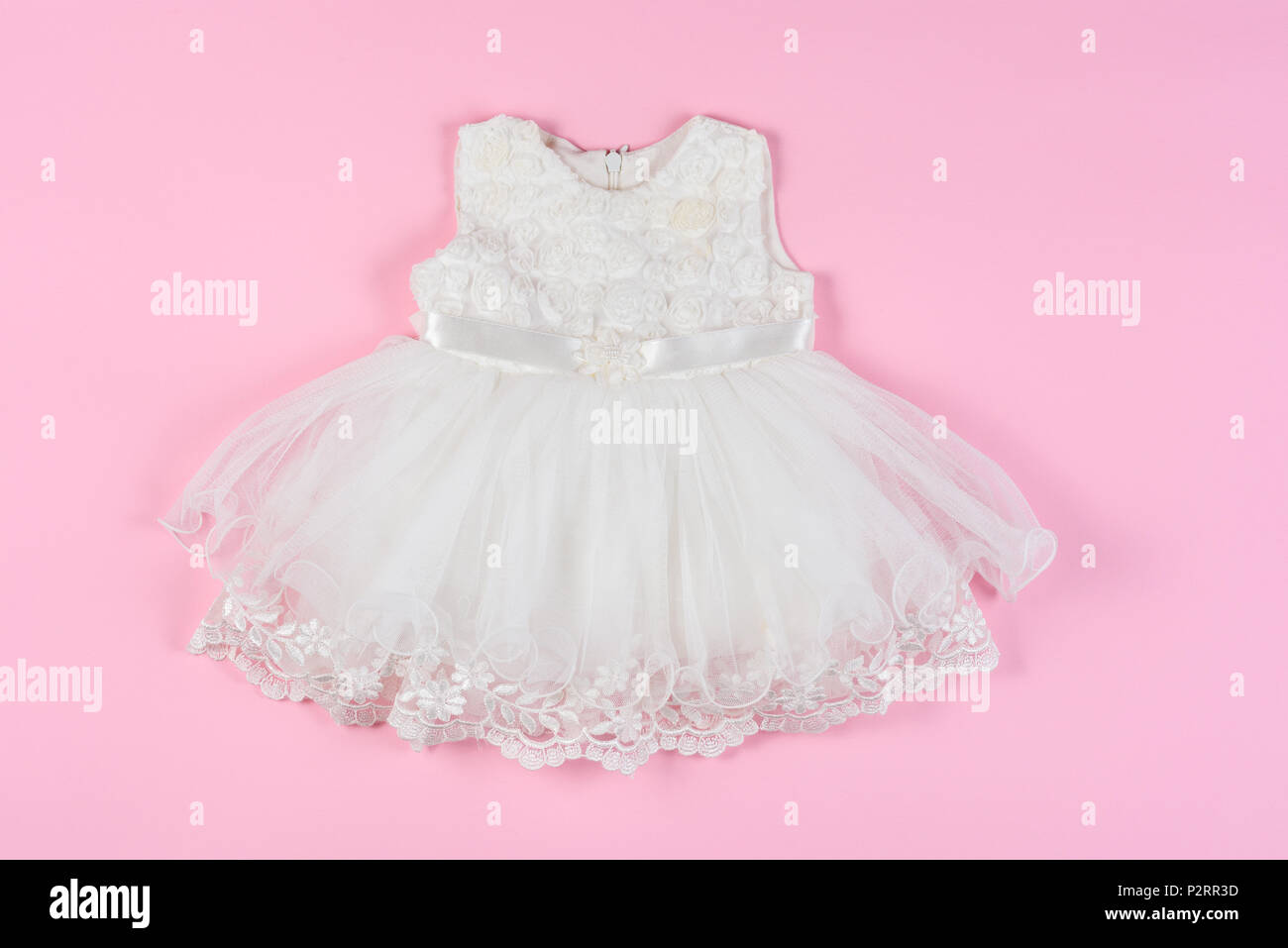 43d6e825599d White baby dress with flowers on a pink background. Concept of ...