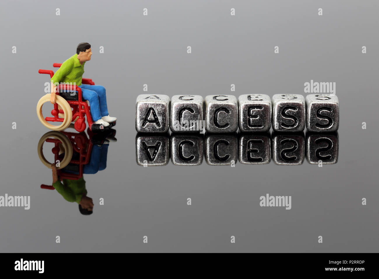 Miniature scale model man in a wheelchair with the word access on beads reflected on a dark background - Stock Image