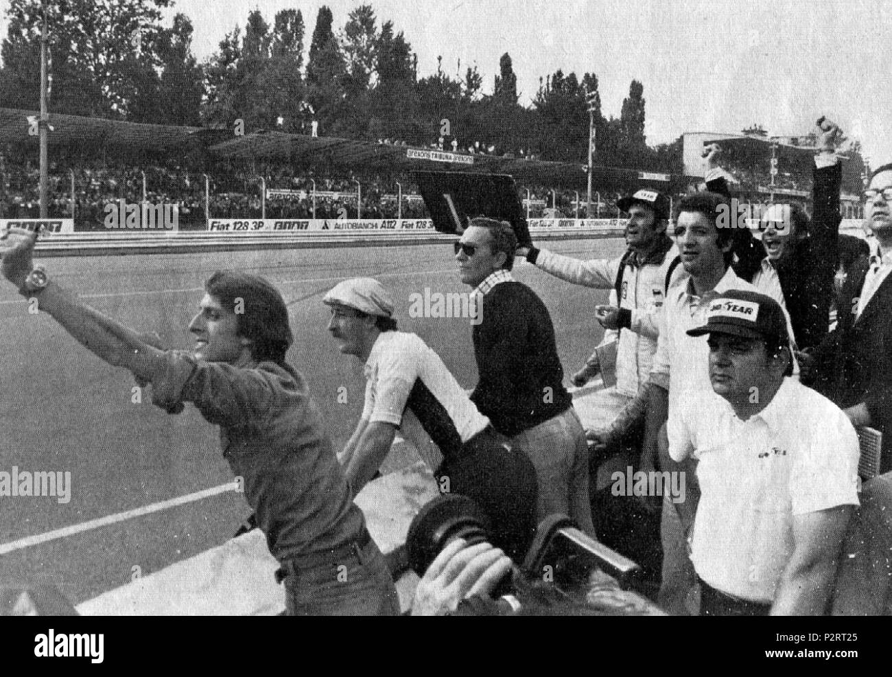 """. Italiano: Monza, Autodromo Nazionale, 7 settembre 1975. XLVI Gran Premio d'Italia. Il box della Scuderia Ferrari, a pochi giri dal termine, incita dal muretto il suo pilota, lo svizzero Clay Regazzoni, in testa alla corsa; si riconosce (a sinistra) il team manager della scuderia, Luca Cordero di Montezemolo. """"Cinquantesimo giro, Regazzoni sbuca dalla parabolica, ed i cartelli sono ormai superflui. Dal box Ferrari si alzano le braccia in segno di vittoria, il gesto di Luca Montezemolo è eloquente.""""  . 7 September 1975. Unknown 2 1975 Italian GP - Ferrari box rejoices Stock Photo"""