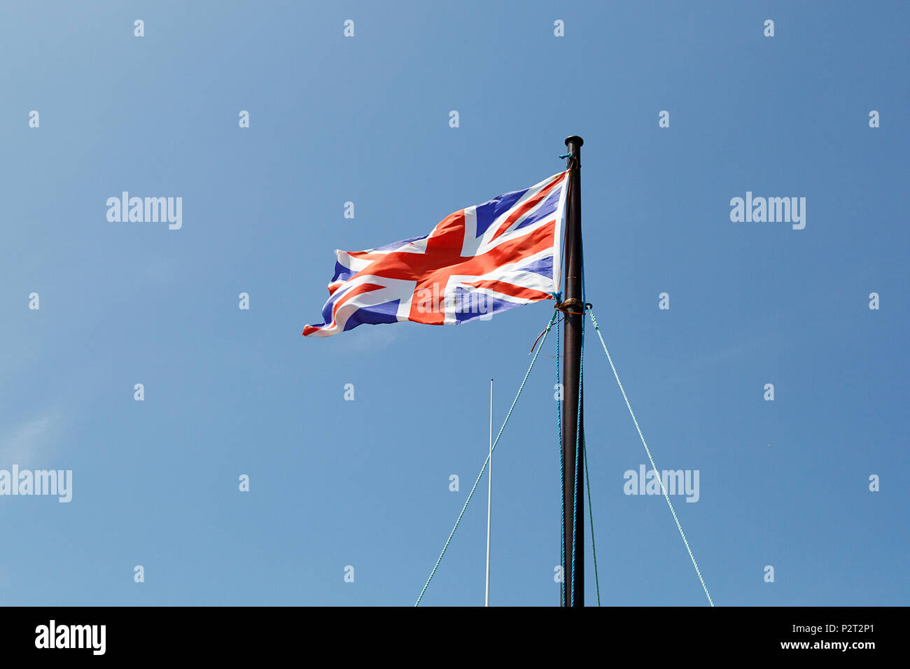 Union Jack flag flying in the breeze against a blue sky background. Stock Photo
