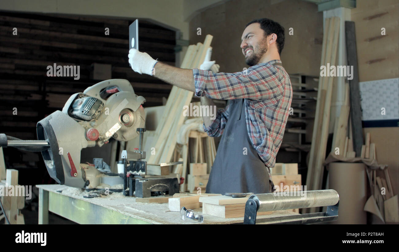 Carpenter makes selfie near woodworking machines in carpentry shop. Stock Photo