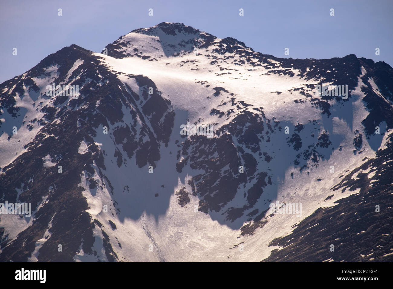 This is a mountain summit you can see from the city of Ushuaia. It belongs to the Martial mountains. Snow has fallen and sticks to the mountain. Stock Photo