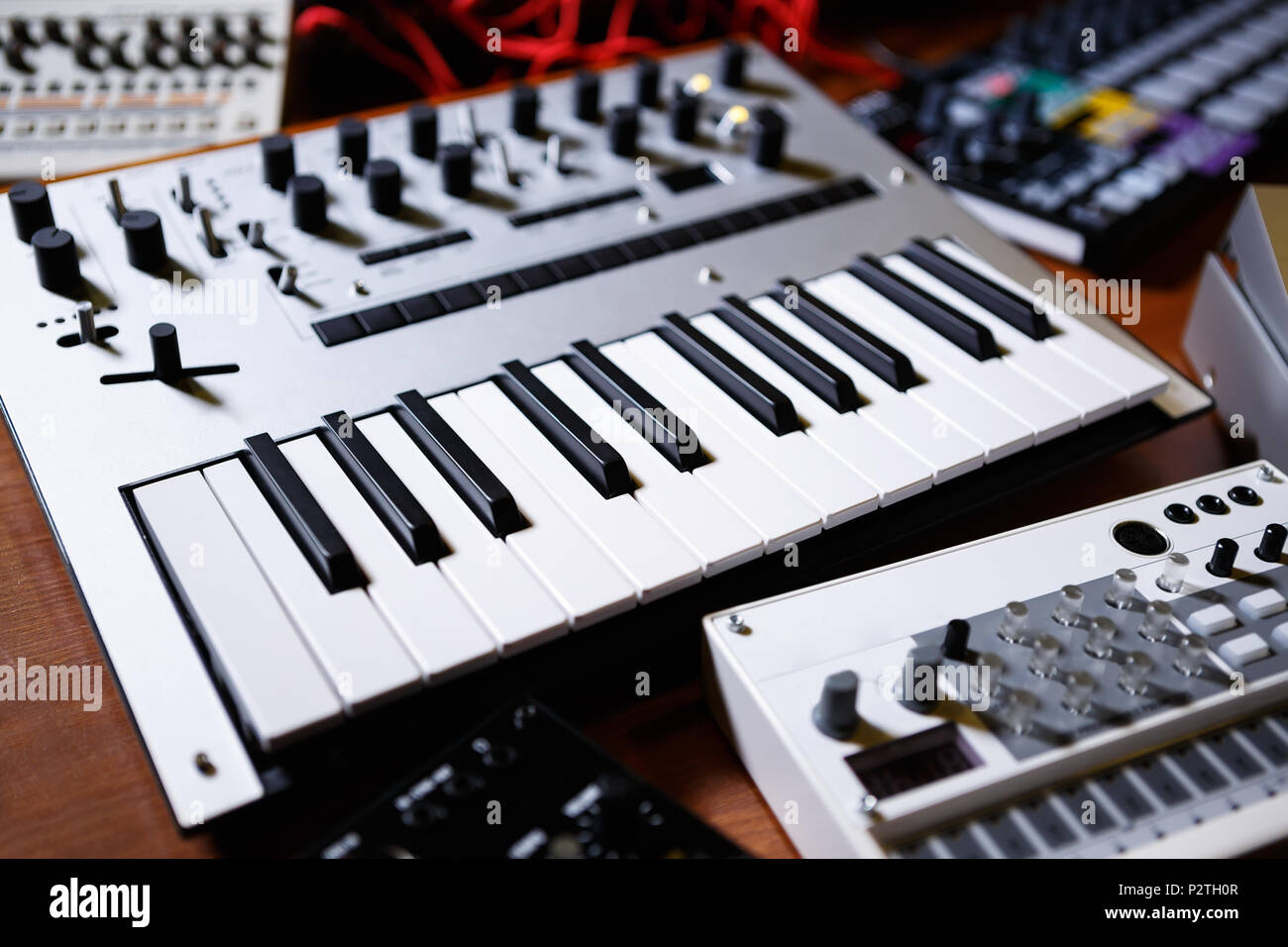 Buy synthesizer in dj shop.Professional electronic midi keyboard with black and white piano keys in music store.Audio equipment for musical production - Stock Image
