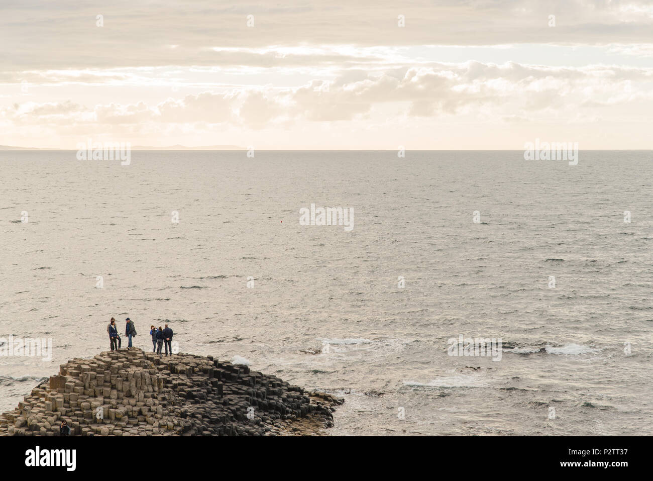 People standing on the rocks next to the ocean at Giant's Causeway in Northern Ireland. - Stock Image