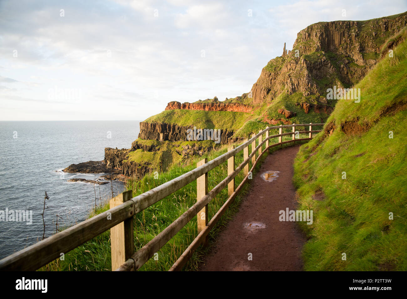A path on the side of a mountain by the ocean in Northern Ireland. - Stock Image