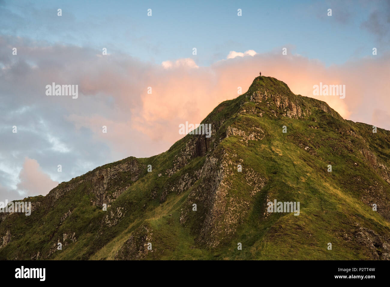 Landscape view of a distant person at the peak of a mountain near Giants Causeway in Northern Ireland. - Stock Image