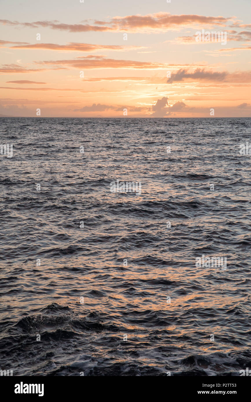 A sunset next to the ocean at Giants Causeway in Northern Ireland. - Stock Image