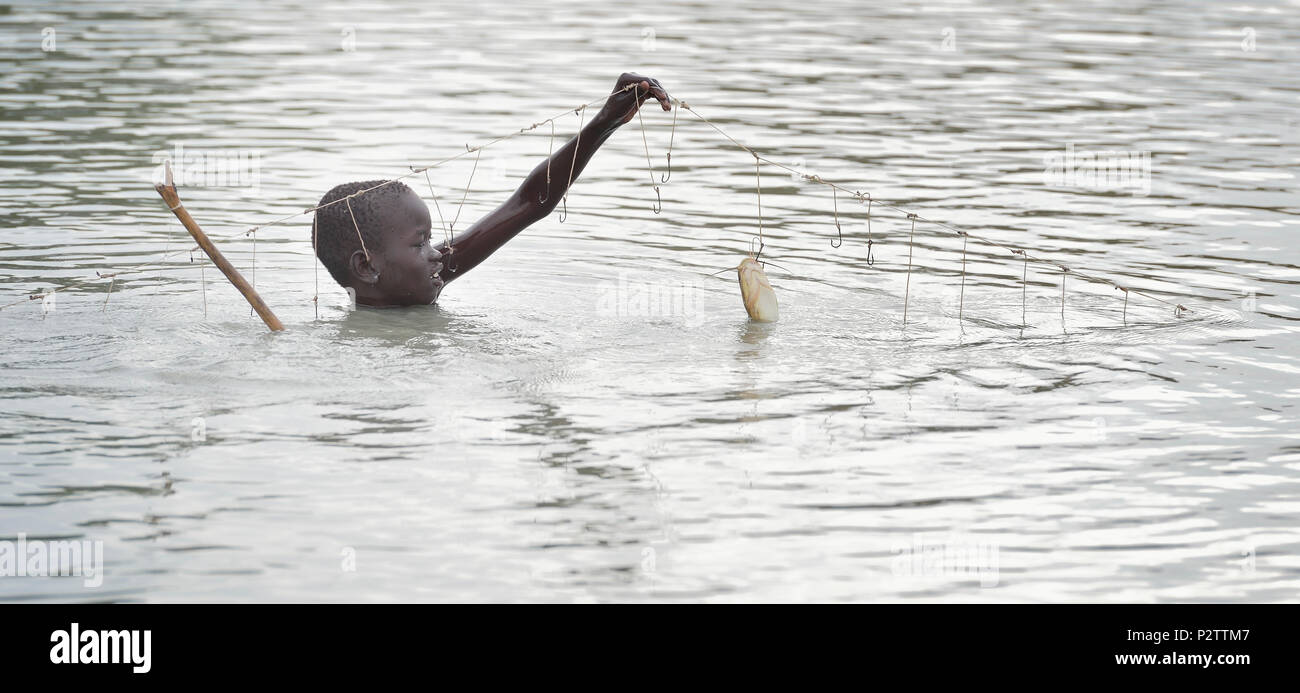 Choul Majak, 9, catches fish in Poktap, a town in South Sudan's Jonglei State where conflict, drought and inflation have caused severe food insecurity. - Stock Image