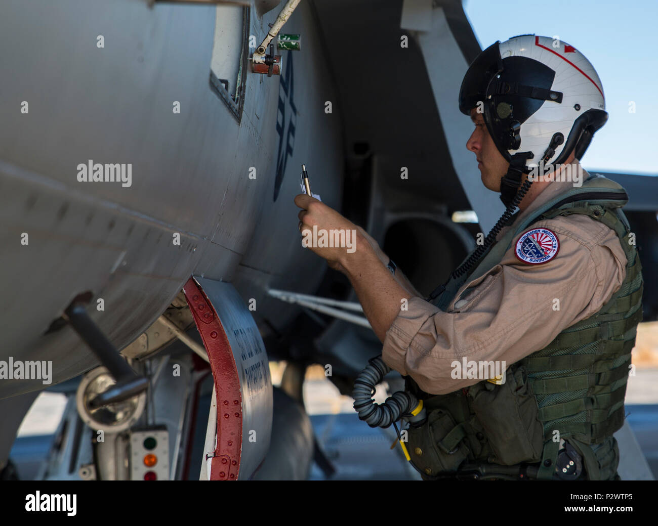 U.S. Marine Corps Capt. Daniel Lane, Marine Fighter Attack Squadron (VMFA) 122 pilot, conducts a preflight check on an F/A-18C Hornet during Exercise Pitch Black 2016 at Royal Australian Air Force Base Tindal, Australia, Aug. 1, 2016. Pitch Black 16 is a biennial, three week, multinational, large-force training exercise hosted by RAAF Tindal. As the training progresses, the U.S. pilots will also get the opportunity to fly with Canada, France, Germany, Indonesia, Netherlands, New Zealand and Thailand. (U.S. Marine Corps photo by Cpl. Nicole Zurbrugg) - Stock Image