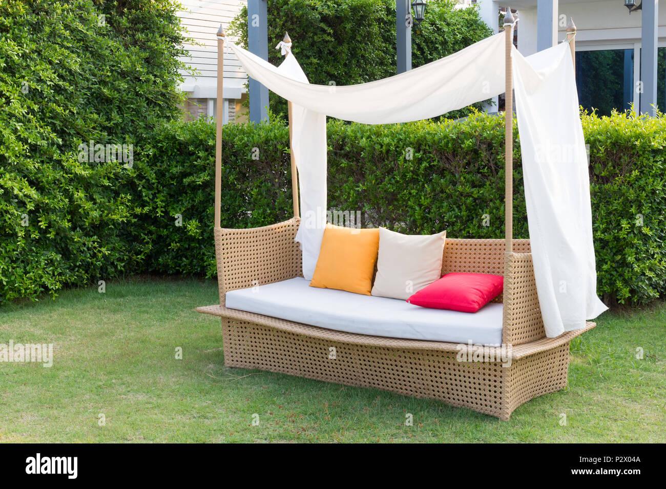 Modern sofa  wicker and color pillows in the garden. Stock Photo