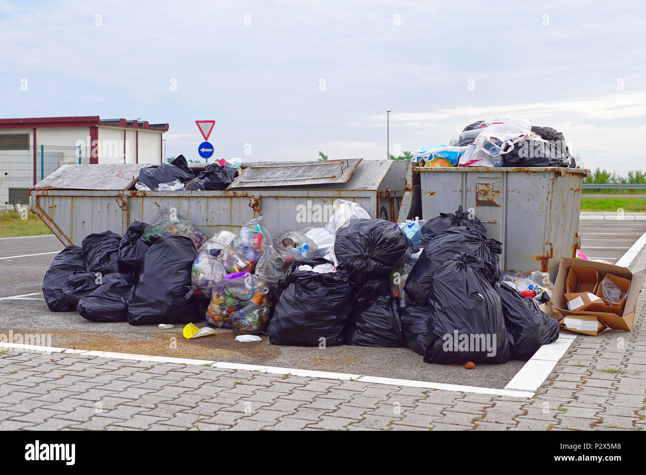 Overflow of garbage litter and empty trash can - Stock Image