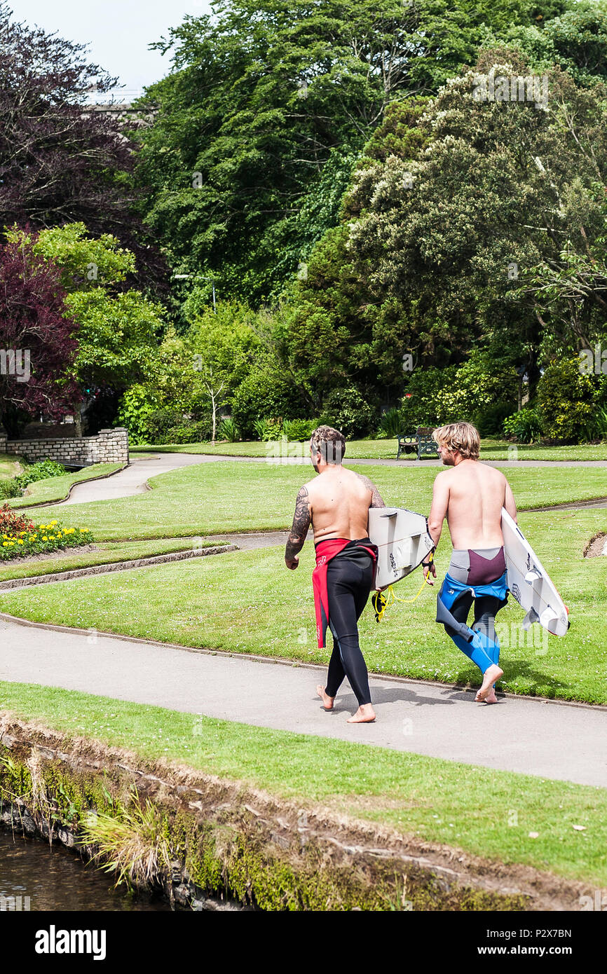 Two surfers carrying their surfboards walking through a landscaped garden in Newquay in Cornwall. - Stock Image