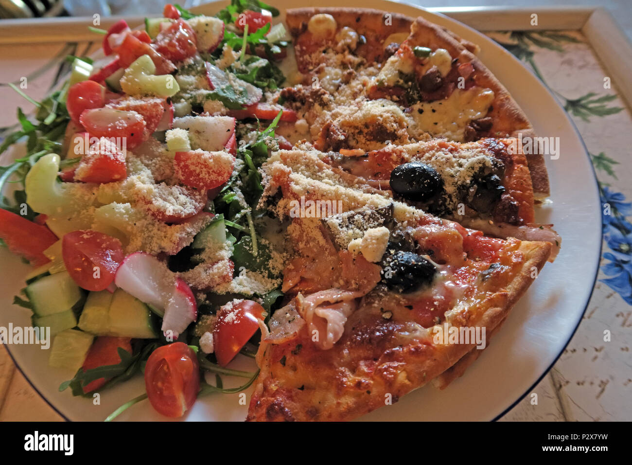 High caloriie home pizza with salad, Parmesan cheese - Stock Image