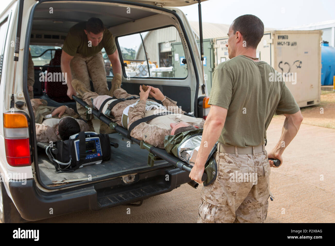 U.S. Navy Lt. Cmdr. Robert Oldt, an Emergency Physician, and Cpl. Kenneth Bourgeois, a Refrigeration/Air Conditioning Technician, both with Special Purpose Marine Air-Ground Task Force-Crisis Response-Africa unload a simulated casualty for patient movement and triage during a mass casualty drill, August 1, 2016. SPMAGTF-CR-AF Medical personnel were put to the test with realistic medical emergencies and taught to improvise during unforeseen circumstances to enhance mission readiness in the event of a future crisis. (U.S. Marine Corps Photo by Sgt. Kassie McDole.) Stock Photo