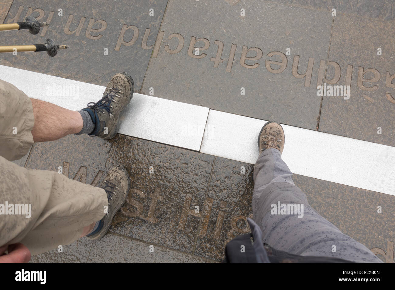 Two walkers crossing the West Highland Way finish line in Fort William, Scotland, UK - Stock Image