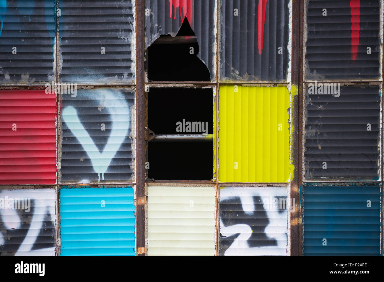 Broken urban window panes made artistic with paint - Stock Image